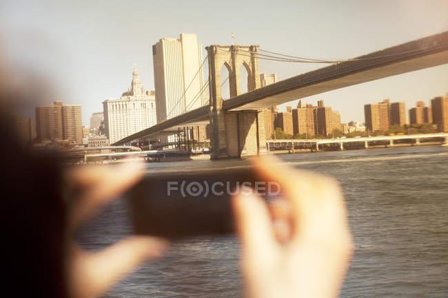 Des mains qui photographient le pont urbain et le paysage urbain — Photo de stock