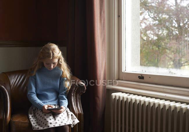 Ragazza navigando tablet digitale in poltrona a casa — Foto stock