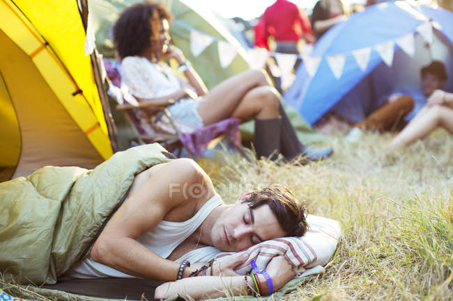 Man sleeping in sleeping bag outside tent at music festival — Stock Photo