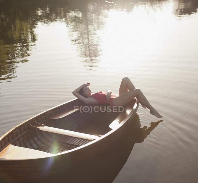 Serene woman sunbathing in boat on lake — Stock Photo