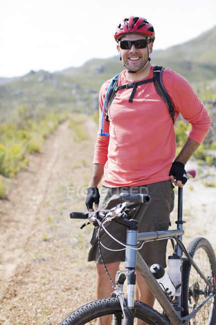 Mountain biker sorrindo no caminho da sujeira — Fotografia de Stock