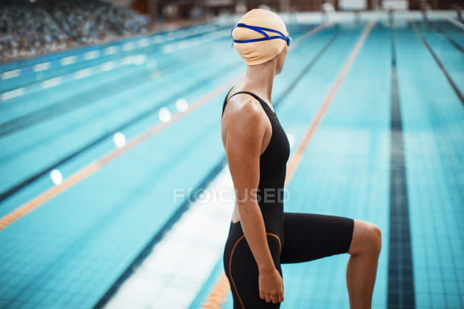 Swimmer standing at poolside — Stock Photo