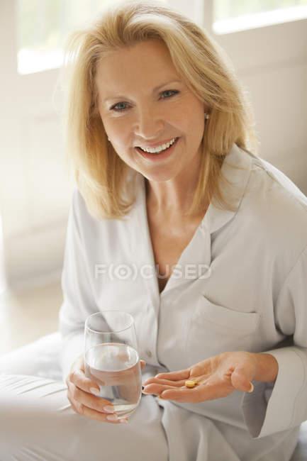 Портрет посміхаючись жінка холдингу таблетки і склянку води — стокове фото