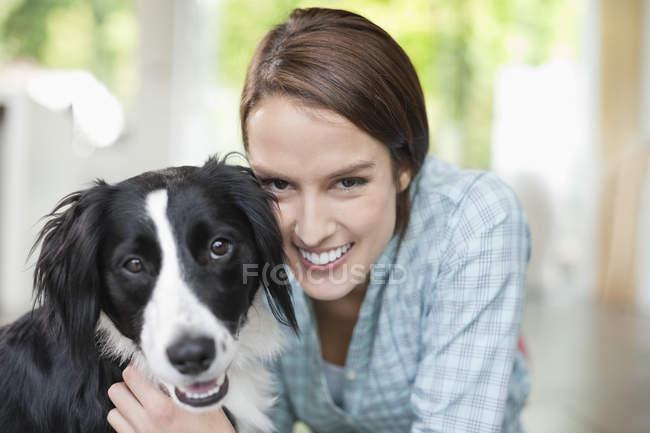 Усміхаючись жінка Петтінг собака в сучасному будинку, крупним планом — стокове фото