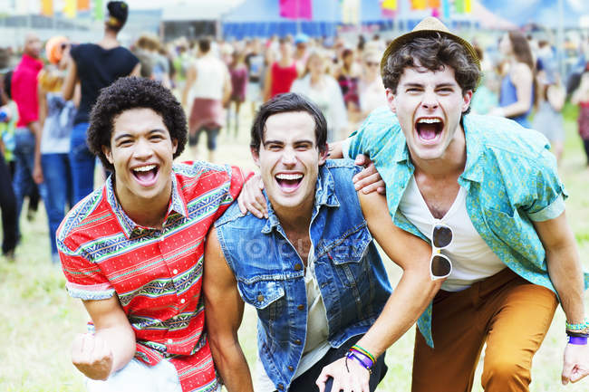 Enthusiastic men cheering at music festival — Stockfoto