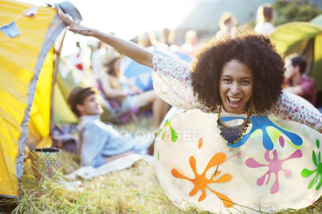 Портрет игривой женщины, лежащей на надувном стуле снаружи палаток на музыкальном фестивале — стоковое фото