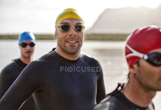 Confident and strong triathlete in wetsuit smiling in water — Stock Photo