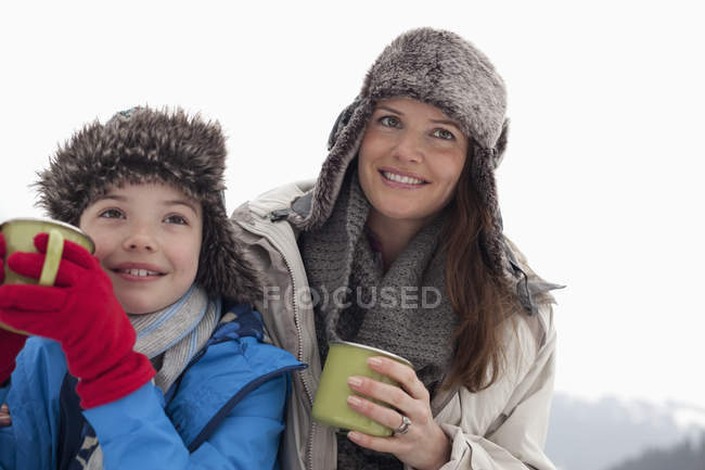 Happy mother and son in fur hats drinking hot chocolate — Stock Photo