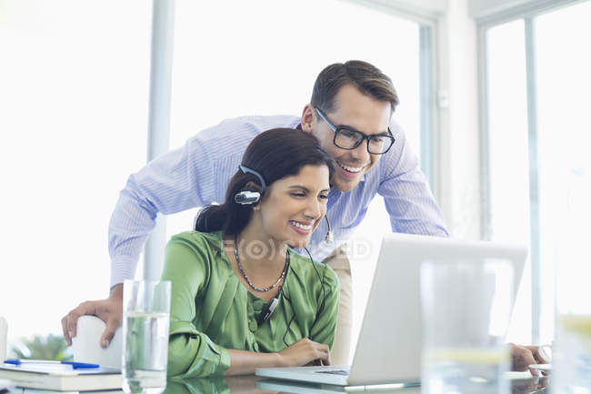 Business people using laptop together at desk at modern office — Stock Photo