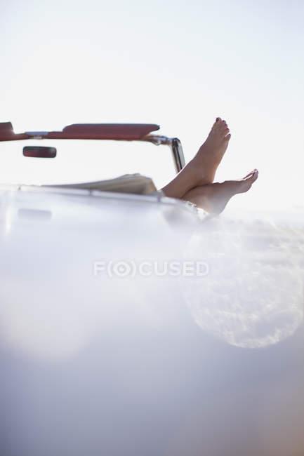 Женщина ноги, опираясь на кабриолет — стоковое фото