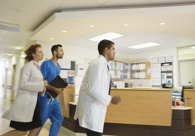 Personal del hospital corriendo por pasillo - foto de stock