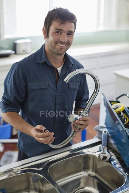 Искусный кавказский сантехник, работающий на кухонной раковине — стоковое фото