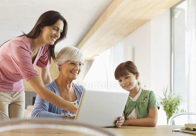Three generations of women using tablet computer — Stock Photo