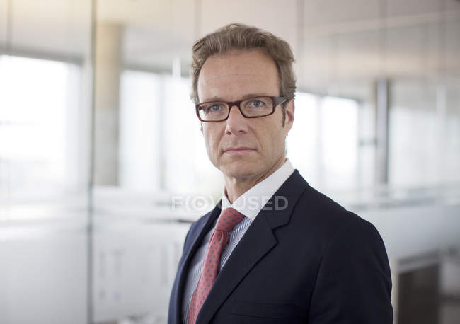 Businessman standing in hallway at modern office — Stock Photo