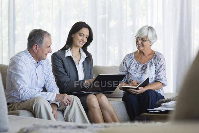 Consulente finanziario che parla con coppia sul divano — Foto stock