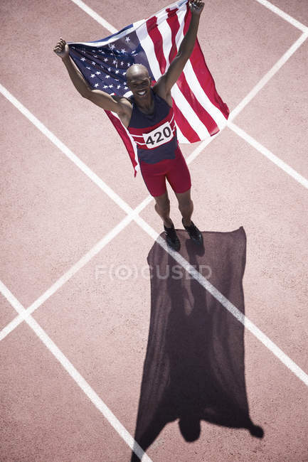 Atleta di atletica leggera con bandiera americana in pista — Foto stock