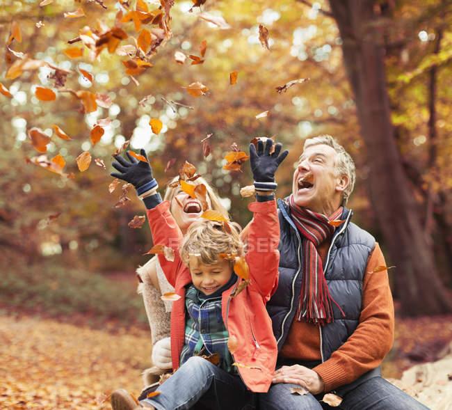 Старшая пара играет с внуком в осенние листья — стоковое фото
