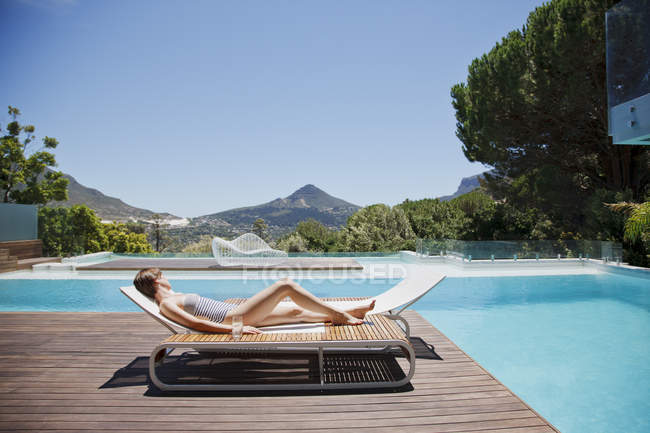 Woman sunbathing on lounge chair next to luxury swimming pool with mountain view — Stock Photo