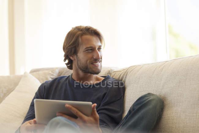 Jeune homme attrayant en utilisant tablette sur le canapé — Photo de stock