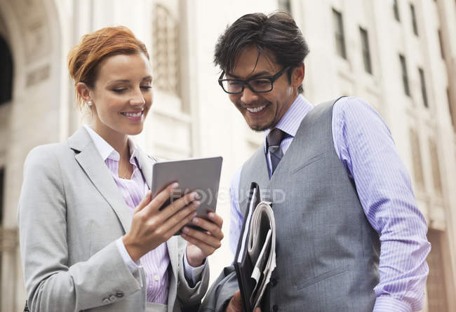 Business people using tablet computer on city street — Stock Photo