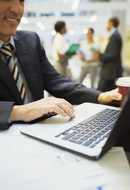 Empresário, trabalhando no laptop, no prédio de escritórios — Fotografia de Stock