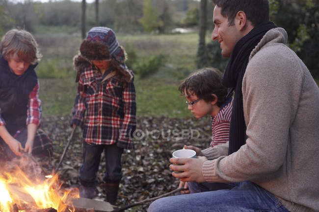 Father and children sitting around bonfire at nature — Stock Photo