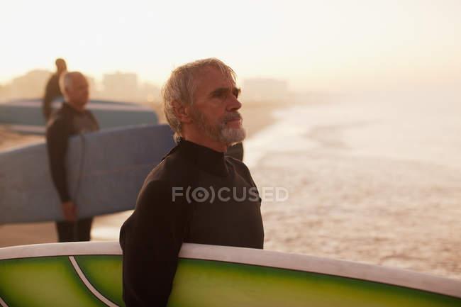 Старшие серферы с досками на пляже — стоковое фото