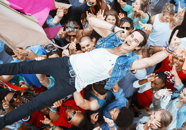 Performer singing and crowd surfing at music festival — Stock Photo