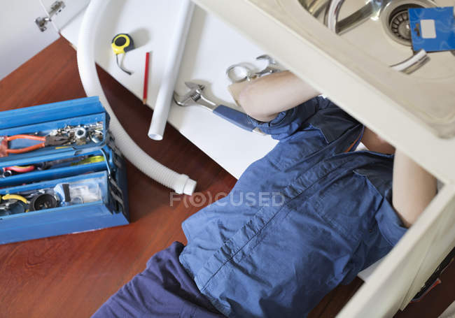 Skillful caucasian plumber working on pipes under sink — Stock Photo