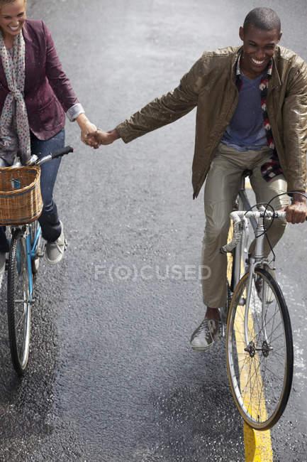 Счастливая пара, держась за руки и катаясь на велосипедах — стоковое фото