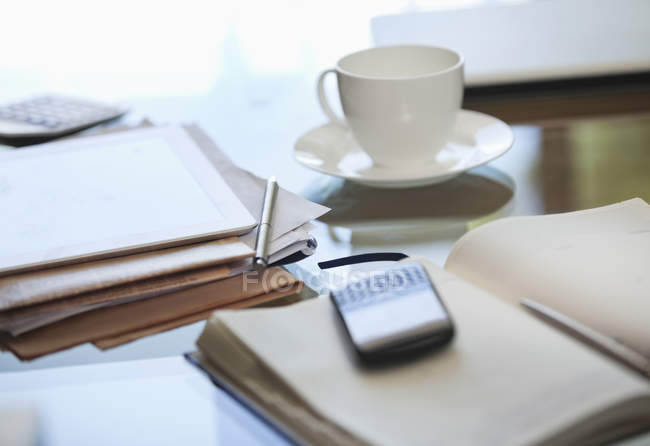 Notebook, cell phone and cup of coffee on desk — Stock Photo