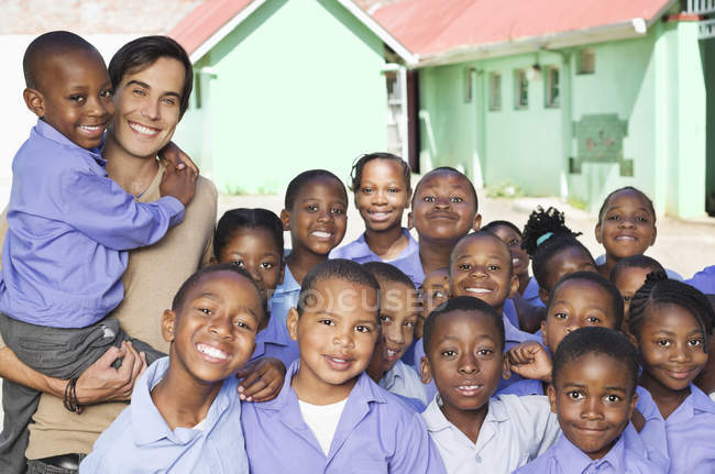 African american students and teacher smiling outdoors — Stock Photo