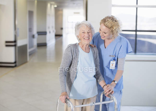 Nurse helping senior patient with walker in hospital corridor — Stock Photo