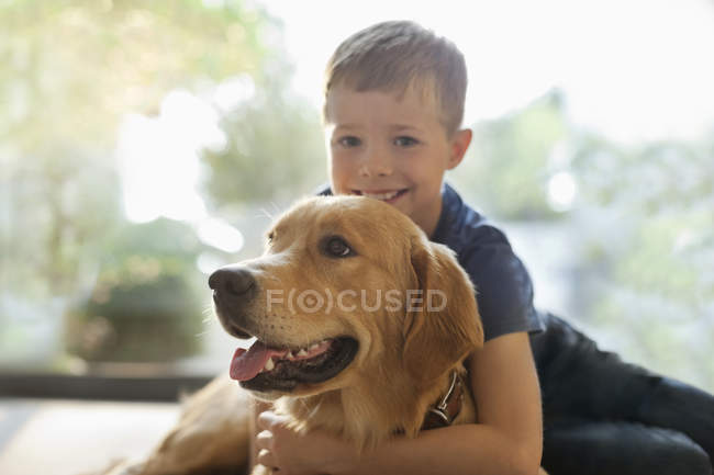 Sorrindo menino abraçando cão dentro de casa — Fotografia de Stock