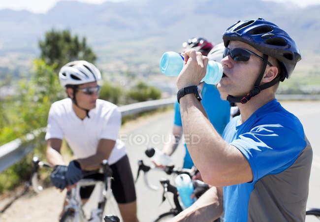 Agua potable para ciclistas en carretera rural - foto de stock