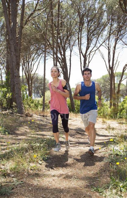 Couple running on dirt path — Stock Photo