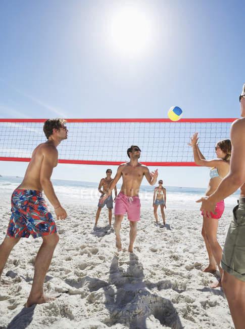Glückliche kaukasische Freunde spielen Beachvolleyball — Stockfoto