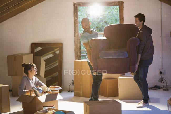 Amigos moviendo muebles en un nuevo hogar - foto de stock