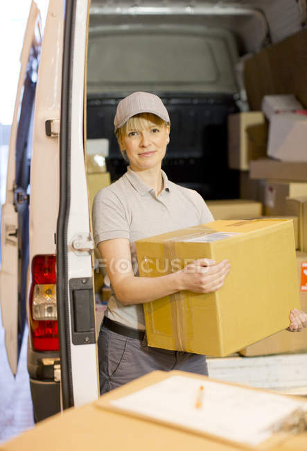 Delivery girl unloading boxes from van — Stock Photo