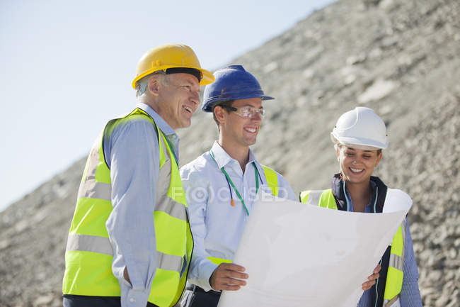 Business people reading blueprints in quarry — Stock Photo