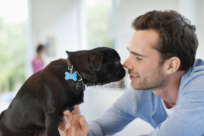 Man and dog touching noses indoors — Stock Photo