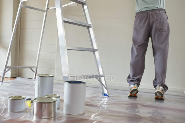 Cropped image of man painting in room with ledder — Stock Photo