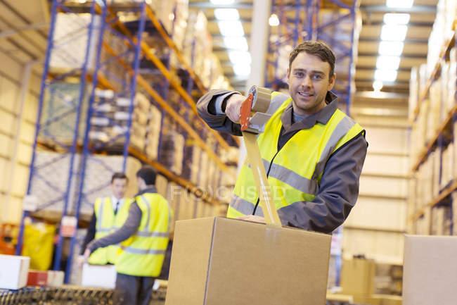 Worker taping cardboard box in warehouse — Stock Photo