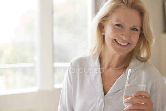 Портрет усміхається жінка, питне скло води — стокове фото
