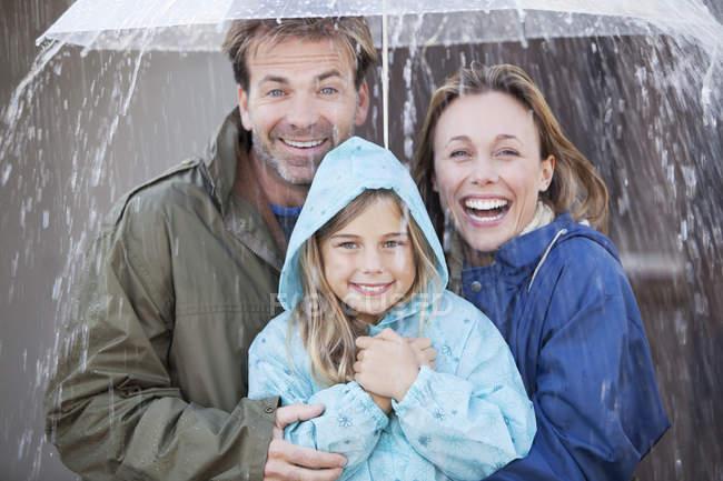 Портрет ентузіазму родини під парасолькою в злива — стокове фото