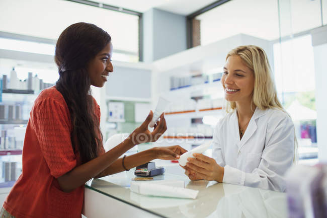 Woman discussing skincare product with pharmacist in drugstore — Stock Photo