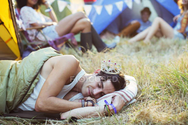 Man in tiara sleeping in sleeping bag outside tents at music festival — Stock Photo