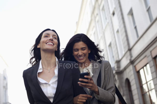 Happy businesswomen text messaging with cell phone — Stock Photo