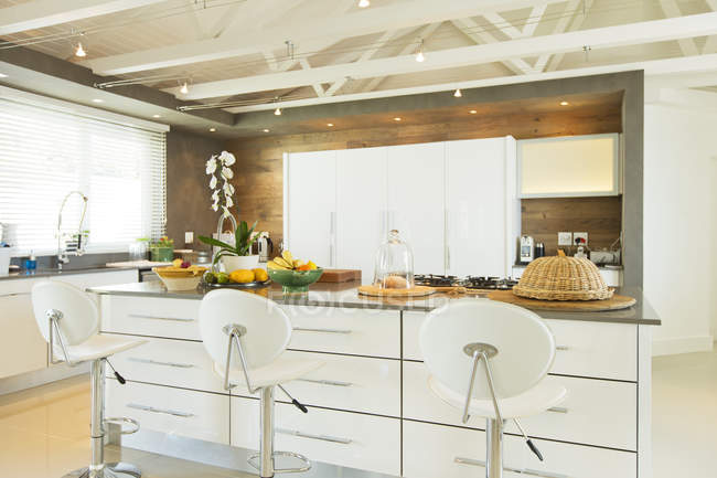 Modern kitchen with barstools indoors — Stock Photo