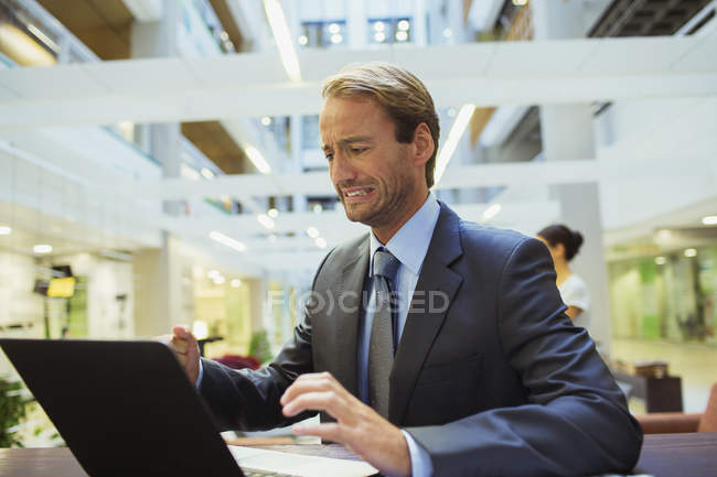 Businessman worried while using laptop in modern office building — Stock Photo